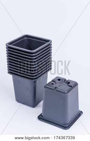 Pile Of Black Plastic Flower Pots Isolated Over White Background