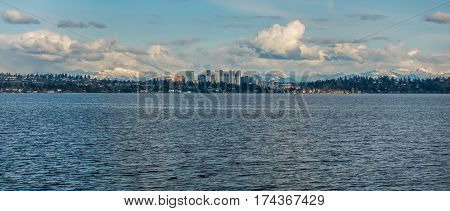 Panorama shot of the skyline of Bellevue Washington with the Cascade Mountains behind.
