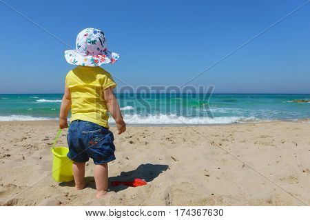 A little baby girl toddler standing in the sand of the beach alone looking towards the sea with a bucket and spade set and a sun hat on a sunny summer day. poster