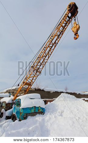 Old mobile construction crane with hook in the snowdrift