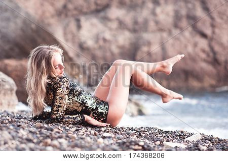 Stylish girl 20-24 year old lying at beach wearing swim suit outdoors. 20s. Summer season.