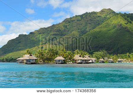Luxury thatched roof bungalows in a honeymoon resort at the waterfront of a pacific lagoon on the polynesian tropical island Moorea near Tahiti in French Polynesia.