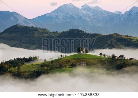 The church of St. Thomas (Sveti Tomaz) on a hilltop in the Slovenian countryside near Skofja Loka surrounded with fog with in the background snow on the peaks of the Slovenian Kamnik Alps during a pink sunrise in Slovenia.