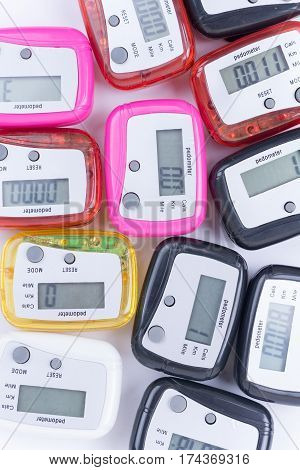 Pile Of Colorful Pedometers Over White Background