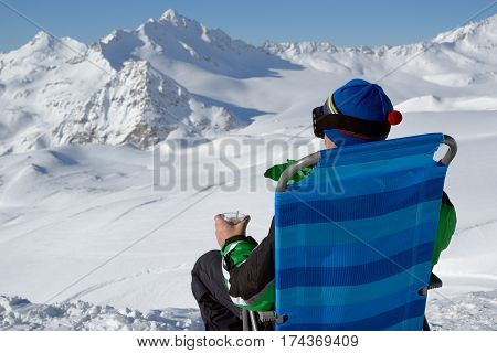 Man in alpine skiing clothes sits in a chaise lounge and looks at mountains a view from a back