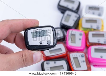Digital Pedometer In The Hand Over Pile Of Pedometers