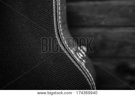 Black guitar case with a wooden background