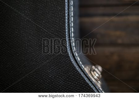 Black guitar case with faded wooden background