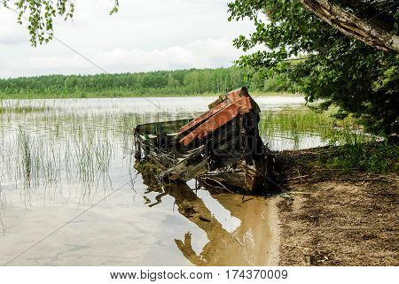A broken boat on the shore of forest lake.