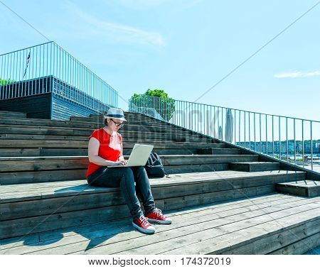 Girl with glasses lying on the steps and using laptop and typing. Freelance concept