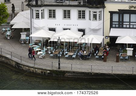 LUCERNE SWITZERLAND - MAY 02 2016: Aerial view towards cafe by the river. Coffee tables and white umbrellas are placed outside building in close proximity to the banks of the River Reuss.