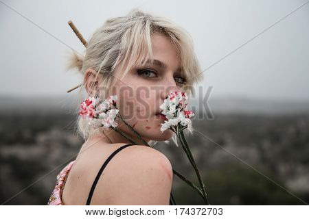 Very pretty Russian young girl smelling bloody white flowers in the field. She is blonde and her eyes are clear. She is dressed like a Chinese girl and the aesthetics is dark.