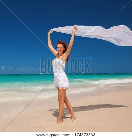 Fashion woman walking on the beach. Happy lifestyle. White sand, blue sky and crystal sea of tropical beach. Vacation at Paradise. Ocean beach relax, travel to islands