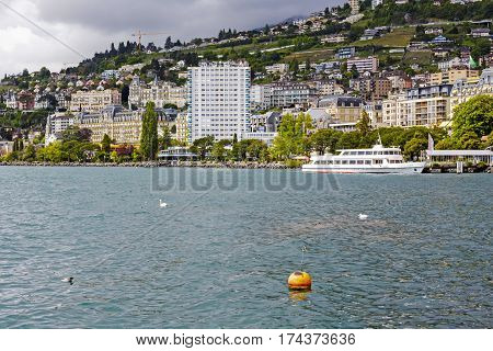 MONTREUX SWITZERLAND - MAY 25 2013: Cityscape on the shore of the Lake Geneva. Among many houses that was built on a the one on the shore of the lake is much higher.