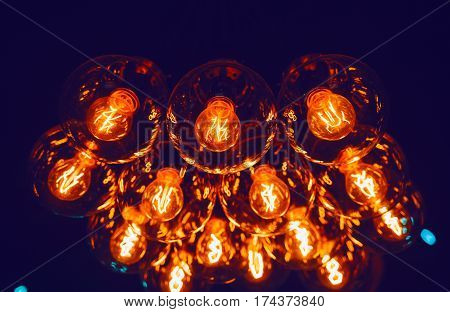 Glowing Leds filament lamps in darkness indoors