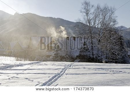 ZAKOPANE POLAND - DECEMBER 29 2010: Residential buildings produce environmental poisoning in the suburban area of secluded part of town known for its wide range of tourist attractions