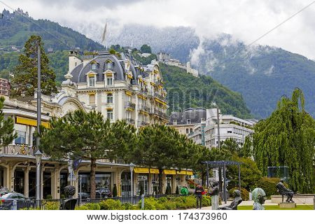 MONTREUX SWITZERLAND - MAY 26 2013: Fabulous building with yellow awnings and the hills on which in the distance you can see the other buildings. More distant hill is covered with snow and fog