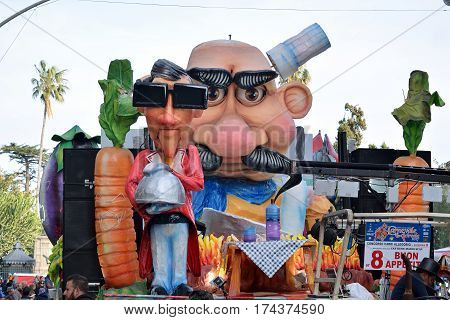 Acireale (CT) Italy - February 28 2017: detail of a allegorical float depicting a man with sunglasses holding a serving bell during the carnival parade along the streets of Acireale.