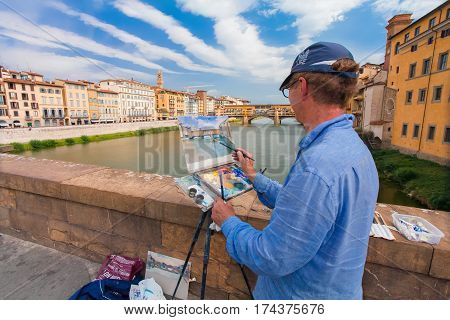 Florence ITALY- September 10 2016: Painter paints the picture of city scenery of medieval stone bridge Ponte Vecchio and the Arno River