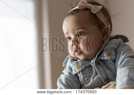 Beautiful baby girl looking away from the camera and making a serious pensive face
