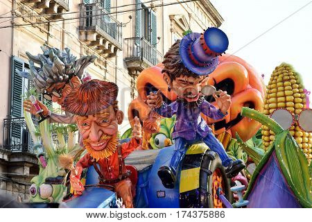 Acireale (CT) Italy - February 28 2017: allegorical float depicting two men with colored dress and hat one red and one purple during the carnival parade along the streets of Acireale.