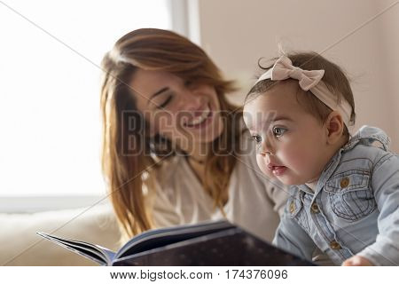 Young mother reading a book to her baby girl smiling and enjoying amazing motherhood moments