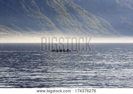 MONTREUX SWITZERLAND - MAY 27 2013: Silhouette of rowers training on the waters of Lake Geneva during a misty day. It is seen in the distance from Montreux on a background of mountains.