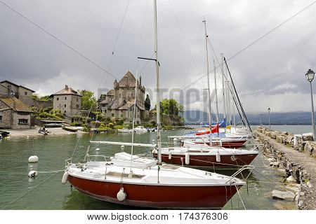 YVOIRE FRANCE - MAY 24 2013: Several sailboats moored along the stone pier at the port on Lake Geneva. On the shore of the lake in the distance a large building that is a medieval castle can be seen