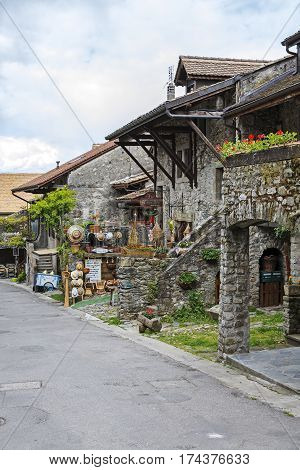 YVOIRE FRANCE - MAY 24 2013: Stone townhouses by the street in medieval town. On a ground floor operate various stores and restaurants that are tourist attraction