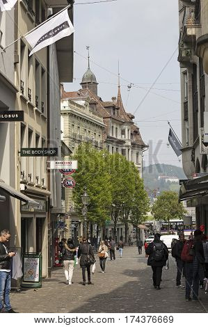 LUCERNE SWITZERLAND - MAY 02 2016: Street view of Lucerne and a people who walk on the cobbled sidewalk. There are many shops located on the ground floor of buildings.