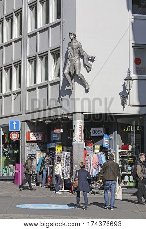 LUCERNE SWITZERLAND - MAY 04 2016: Street view of Lucerne and a people who walk on in front of the kiosk that is located on a corner. Female statue is placed on a building facade over the kiosk.
