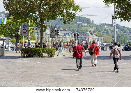 LUCERNE SWITZERLAND - MAY 08 2016: Street view of the city and a unidentified people who pass through pedestrian crossing and the others walk on sidewalk.