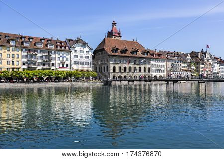 LUCERNE SWITZERLAND - MAY 08 2016: The architecture on the right bank of the river Reuss. The clock tower together with the massive building of town hall can be seen