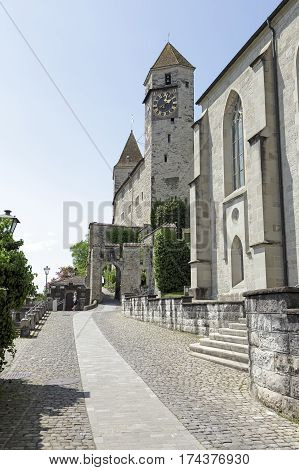 RAPPERSWIL SWITZERLAND - MAY 10 2016:The Castle and its clock tower seen from the side of the narrow street leading to the entrance.