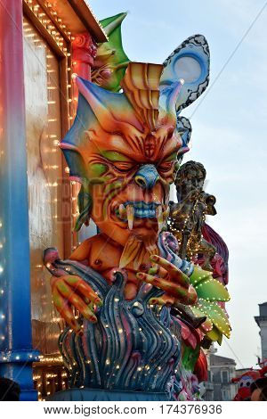 Acireale (CT) Italy - February 28 2017: detail of a allegorical float depicting a colorful demon emerging from colored flames during the carnival parade along the streets of Acireale.