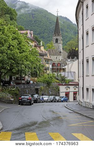 MONTREUX SWITZERLAND - MAY 22 2013: The church tower is over buildings in a background of green hills. Here is the street on which before the bend several parked cars can be seen