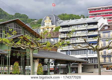 MONTREUX SWITZERLAND - MAY 23 2013: The diversity of architecture in the city is shown in the background of forested hills and cloudy sky. On the roof of one of the houses the national flag flutters