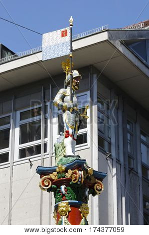 LUCERNE SWITZERLAND - MAY 06 2016: The figure of a man in the helmet with a flag and a sword who stands on top of the colorful and ornate pillar of the Fritschi Fountain.