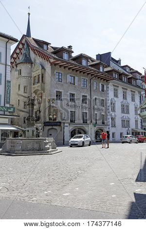 LUCERNE SWITZERLAND - MAY 08 2016: The historic building and pharmacy store on a ground floor and a stone fountain on the square where a few people and cars can be seen
