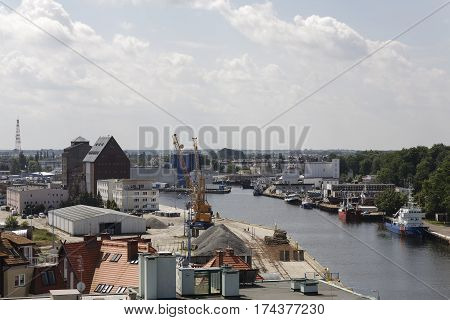 KOLOBRZEG POLAND - JUNE 22 2016: The port channel that leads to the port and a few boats are moored at the wharf. Various building can be seen around