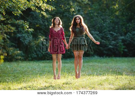 Two young smiling women levitate in the park