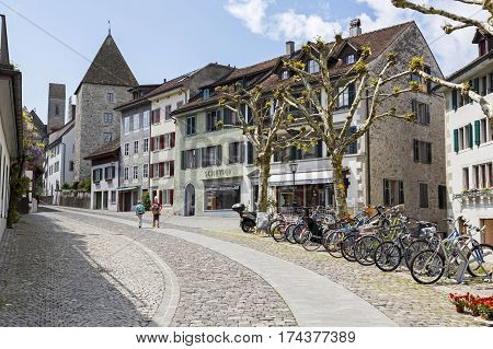 RAPPERSWIL SWITZERLAND - MAY 10 2016: The narrow street leads uphill to a castle. Along a cobblestoned road there are historical buildings and parked bicycles and two people can be seen