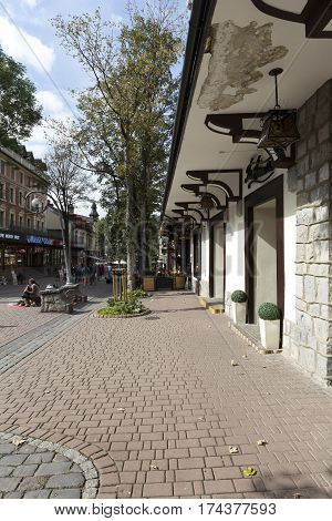 ZAKOPANE POLAND - SEPTEMBER 23 2016: The view along the white facade of the building which is on the street Krupowki. Several people can be seen in a far distance