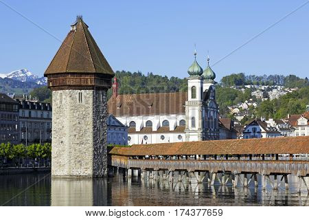 LUCERNE SWITZERLAND - MAY 05 2016: Three of most recognizable landmarks in the city are the octagonal tower and roofed Chapel Bridge and the Jesuit Church