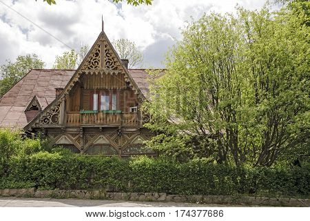 ZAKOPANE POLAND - MAY 23 2009: Timber house with a richly decorated facade is seen surrounded by greenery. It is the wooden villa dating from 1893 called Goplana