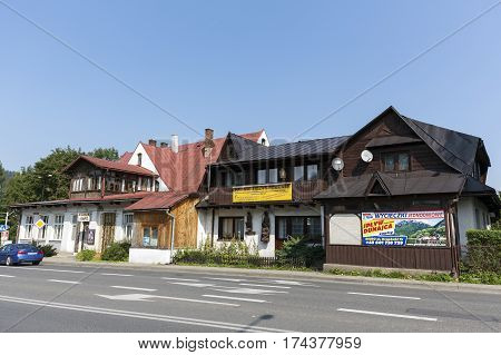 ZAKOPANE POLAND - SEPTEMBER 13 2016: Two historical buildings with sloping roofs and with elements of the style of the region are located by the street.