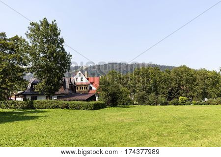 ZAKOPANE POLAND - SEPTEMBER 13 2016: Two classic houses that was built in the style of the region are hidden among bushes and trees and can be seen behind the green meadow
