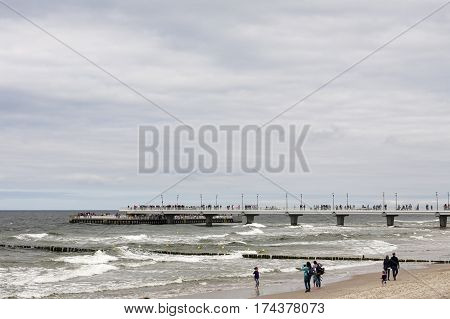 KOLOBRZEG POLAND - JUNE 26 2016: During a cloudy and windy day several vacationers enjoy walking on a sand beach along the coast of the Baltic Sea