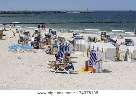 KOLOBRZEG POLAND - JUNE 19 2016: Vacationers enjoy the sunny weather on the sandy beach they are relaxing and sunbathing on the shore of the Baltic Sea many of them use roofed beach chairs