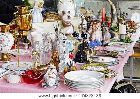 Montreux Switzerland - May 25 2013: Variety of the vessels and ornamental articles put on sale at the famous Covered Market. These objects are exhibited on a long table covered with a tablecloth